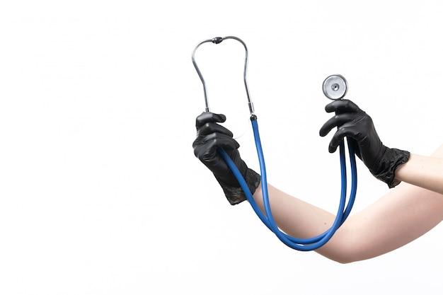 Widok z przodu młoda kobieta trzyma niebieski stetoskop na białym tle
