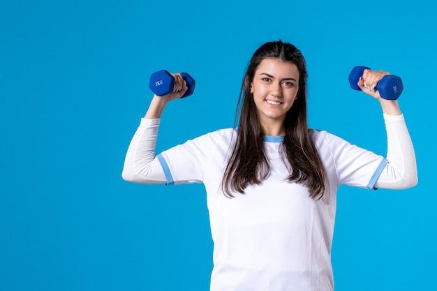 Widok z przodu młoda kobieta trzyma niebieskie hantle na niebieskiej ścianie