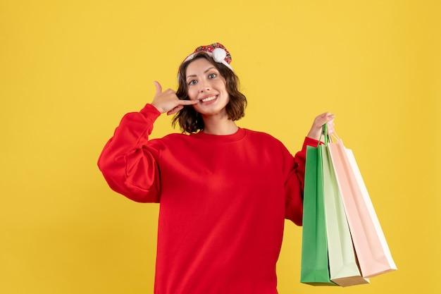 Widok z przodu młoda kobieta trzyma paczki z zakupów na żółto