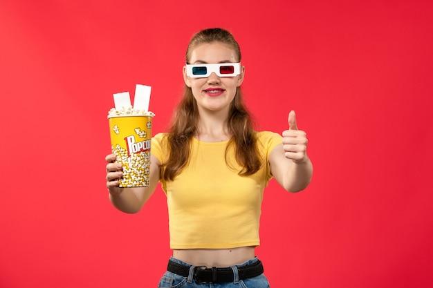 Widok z przodu młoda kobieta trzyma pakiet popcornu d okulary na jasnoczerwonej ścianie kino film kinowy