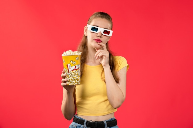 Widok z przodu młoda kobieta trzyma pakiet popcornu d okulary na jasnoczerwonym kinowym filmie kinowym