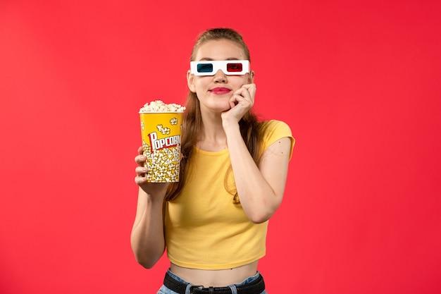 Widok z przodu młoda kobieta trzyma pakiet popcornu in -d okulary na jasnoczerwonym biurku kino kino dziewczyna film