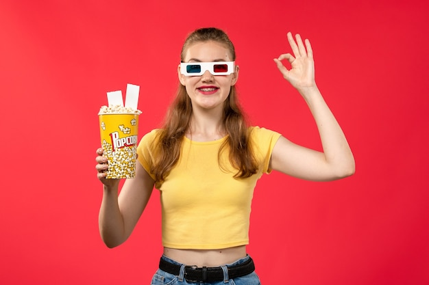 Widok z przodu młoda kobieta trzyma pakiet popcornu na jasnoczerwonej ścianie kina kino dziewczyna film
