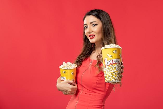 Widok z przodu młoda kobieta trzyma pakiety popcornu na czerwonej powierzchni