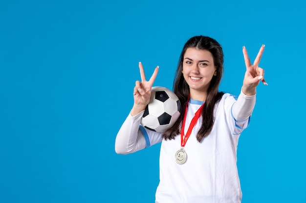 Widok z przodu młoda kobieta trzyma piłkę nożną na niebieskiej ścianie