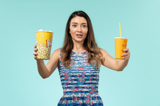 Widok z przodu młoda kobieta trzyma popcorn i napój na niebieskiej powierzchni