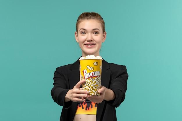 Widok z przodu młoda kobieta trzyma popcorn i ogląda film na jasnoniebieskiej powierzchni