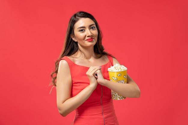 Widok z przodu młoda kobieta trzyma popcorn na czerwonej powierzchni