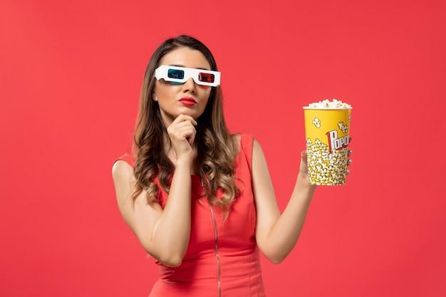 Widok z przodu młoda kobieta trzyma popcorn w d okulary przeciwsłoneczne myśli na jasnoczerwonej powierzchni