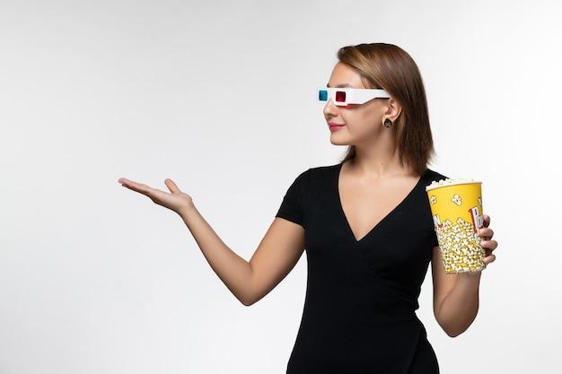 Widok z przodu młoda kobieta trzyma popcorn w d okulary przeciwsłoneczne na białej powierzchni