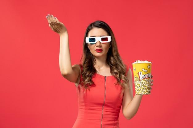 Widok z przodu młoda kobieta trzyma popcorn w d okulary przeciwsłoneczne na czerwonym biurku