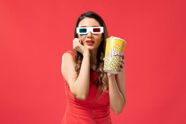 Widok z przodu młoda kobieta trzyma popcorn w d okulary przeciwsłoneczne na jasnoczerwonej powierzchni