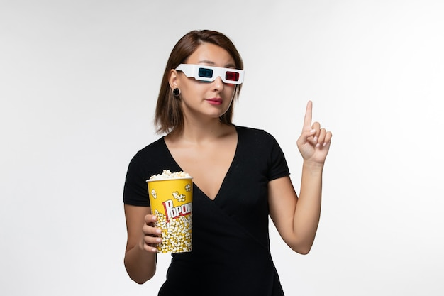 Widok z przodu młoda kobieta trzyma popcorn w d okulary przeciwsłoneczne oglądając film na białej powierzchni