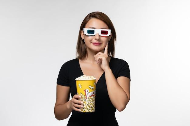 Widok z przodu młoda kobieta trzyma popcorn w d okulary przeciwsłoneczne oglądając film na jasnobiałej powierzchni