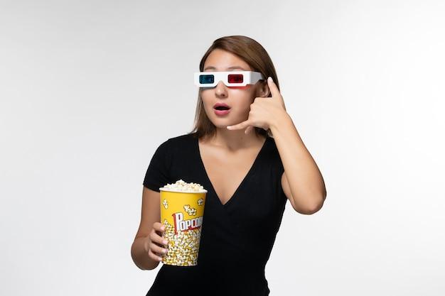 Widok z przodu młoda kobieta trzyma popcorn w d okulary przeciwsłoneczne pozowanie na białej powierzchni