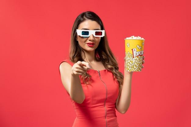 Widok z przodu młoda kobieta trzyma popcorn w d okulary przeciwsłoneczne uśmiechając się na jasnoczerwonej powierzchni