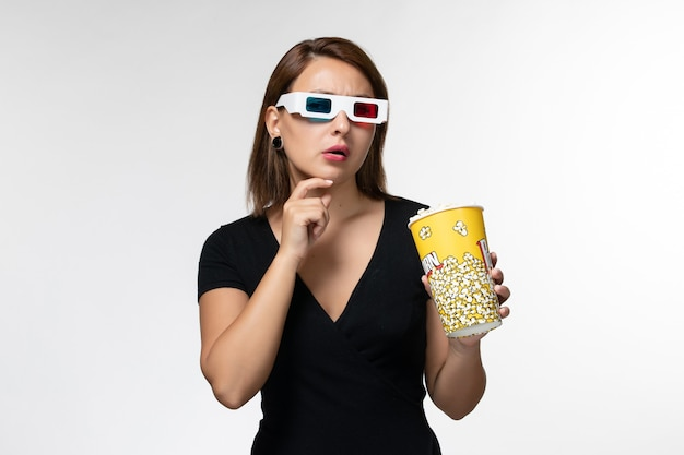 Widok z przodu młoda kobieta trzyma popcorn w okularach przeciwsłonecznych, oglądając film i myśląc na białej powierzchni