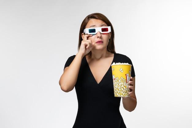 Widok z przodu młoda kobieta trzyma popcorn w okularach przeciwsłonecznych, oglądając film i płacząc na białej powierzchni
