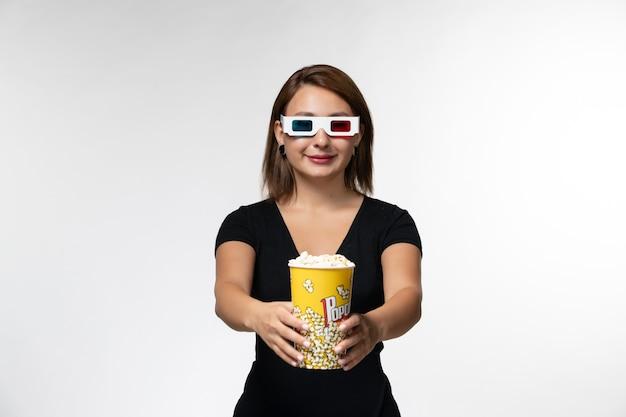 Widok z przodu młoda kobieta trzyma popcorn w okularach przeciwsłonecznych, oglądając film i uśmiechając się na białej powierzchni