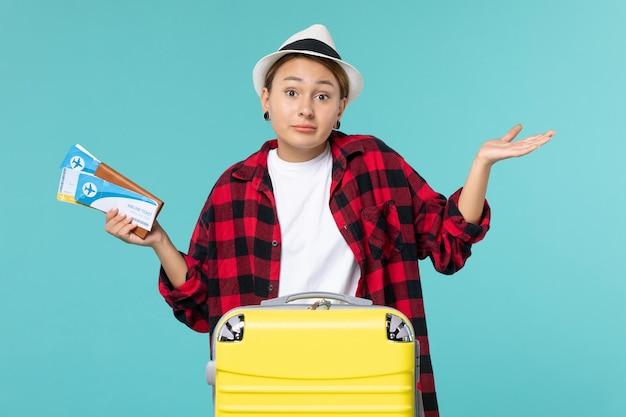 Widok z przodu młoda kobieta trzyma portfel z biletami na jasnoniebieskiej przestrzeni