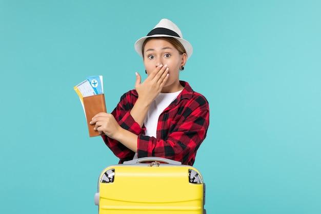 Widok z przodu młoda kobieta trzyma portfel z biletami na niebieskiej przestrzeni