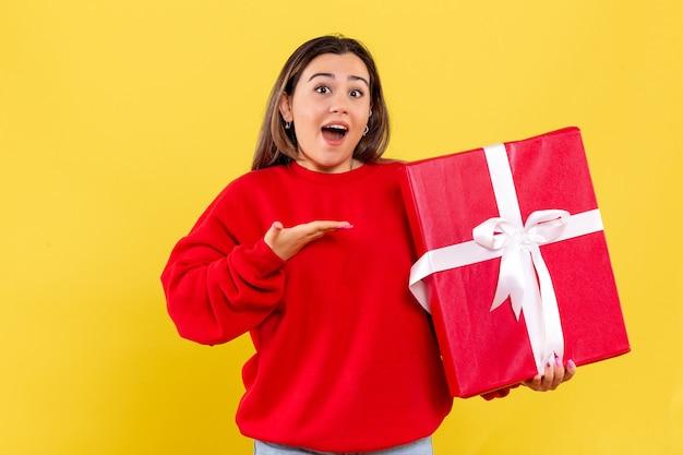 Widok z przodu młoda kobieta trzyma prezent świąteczny na żółtym tle