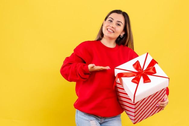 Widok z przodu młoda kobieta trzyma prezent świąteczny uśmiechnięty na żółtym tle