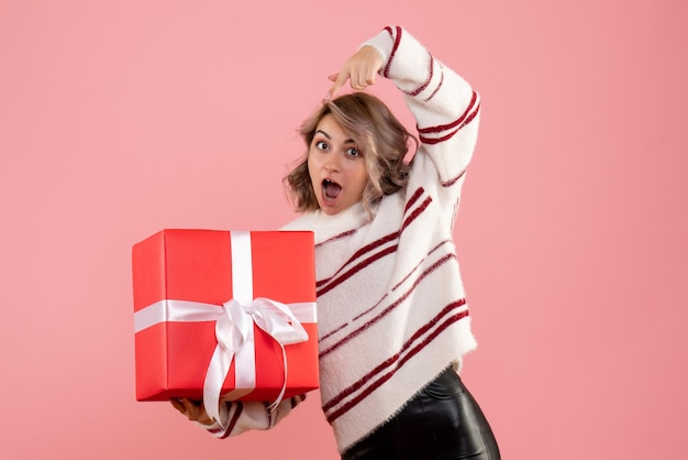 Widok z przodu młoda kobieta trzyma prezent świąteczny