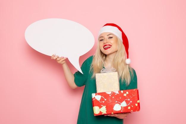 Widok z przodu młoda kobieta trzyma prezenty świąteczne i biały znak na różowej ścianie emocja kobieta prezent kolor śniegu zdjęcie wakacje nowy rok
