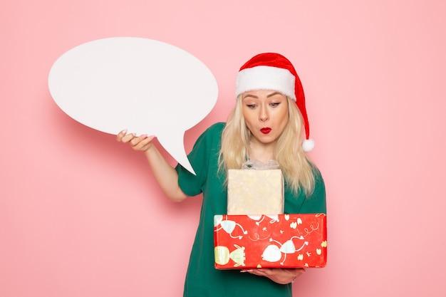 Widok z przodu młoda kobieta trzyma prezenty świąteczne i biały znak na różowej ścianie kobieta prezent kolor zdjęcie wakacje nowy rok