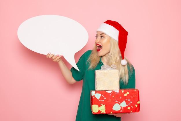 Widok z przodu młoda kobieta trzyma prezenty świąteczne i biały znak na różowej ścianie kobieta prezent śnieg zdjęcie wakacje nowy rok