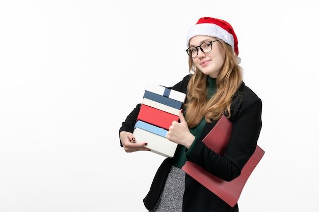 Widok z przodu młoda kobieta trzyma prezenty świąteczne na białej ścianie prezenty boże narodzenie nowy rok