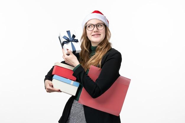 Widok z przodu młoda kobieta trzyma prezenty wakacyjne na białej ścianie prezenty książki nowy rok