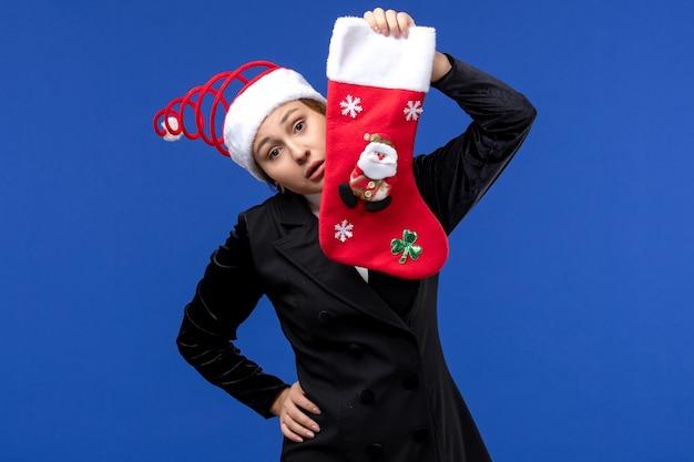 Widok z przodu młoda kobieta trzyma skarpety świąteczne na niebieskiej ścianie kobieta wakacje nowy rok