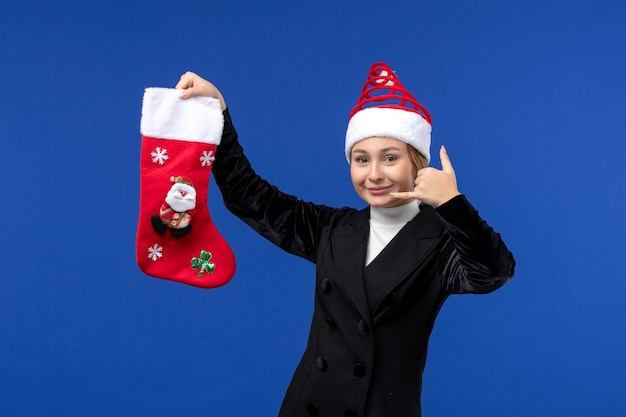 Widok z przodu młoda kobieta trzyma skarpety świąteczne na niebieskiej ścianie wakacje kobieta nowego roku