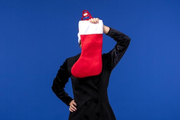 Widok z przodu młoda kobieta trzyma skarpety świąteczne na niebieskiej ścianie wakacje nowy rok człowieka