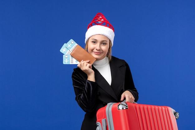 Widok z przodu młoda kobieta trzyma torbę i bilety lotnicze na wycieczkę wakacyjną samolotem o niebieskiej ścianie