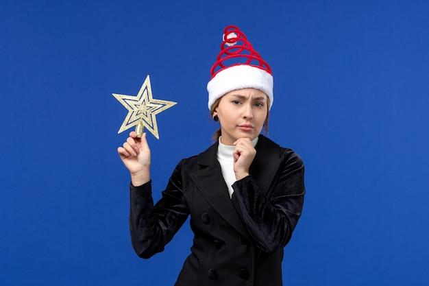 Widok z przodu młoda kobieta trzyma wystrój w kształcie gwiazdy na niebieskiej ścianie kobieta wakacje nowy rok