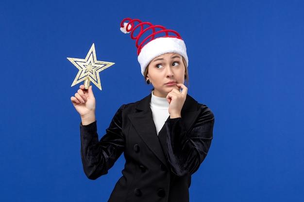 Widok z przodu młoda kobieta trzyma wystrój w kształcie gwiazdy na niebieskiej ścianie nowy rok wakacje kobieta