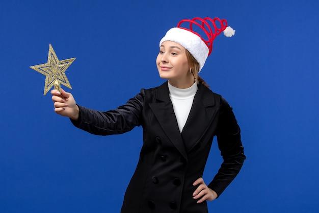 Widok z przodu młoda kobieta trzyma wystrój w kształcie gwiazdy na niebieskiej ścianie święta nowego roku boże narodzenie