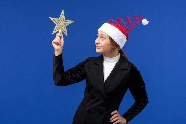 Widok z przodu młoda kobieta trzyma wystrój w kształcie gwiazdy na niebieskiej ścianie święto nowego roku boże narodzenie