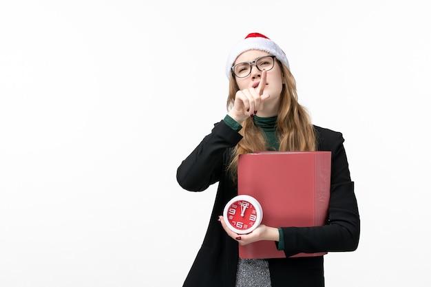 Widok z przodu młoda kobieta trzyma zegar i pliki na białej ścianie lekcja książek uczelni