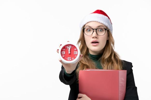 Widok z przodu młoda kobieta trzyma zegar i pliki na białej ścianie lekcje książki uczelni