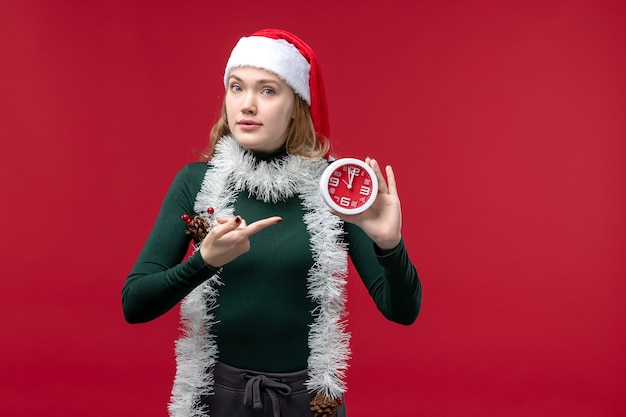 Widok z przodu młoda kobieta trzyma zegar na czerwonym tle