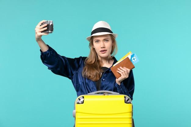 Widok z przodu młoda kobieta trzymając aparat i bilety na niebieskim tle kobieta podróż morze podróżujący samolotem