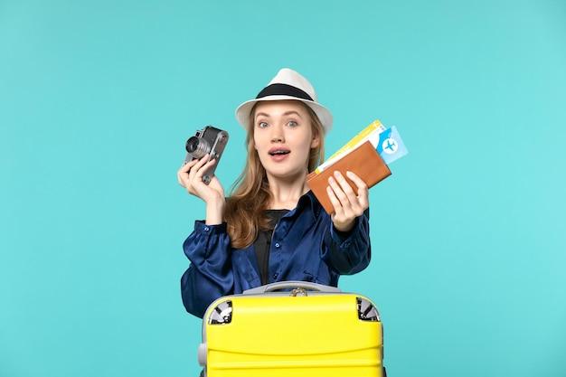 Widok z przodu młoda kobieta trzymając aparat i bilety na niebieskim tle podróż morska podróż samolotem