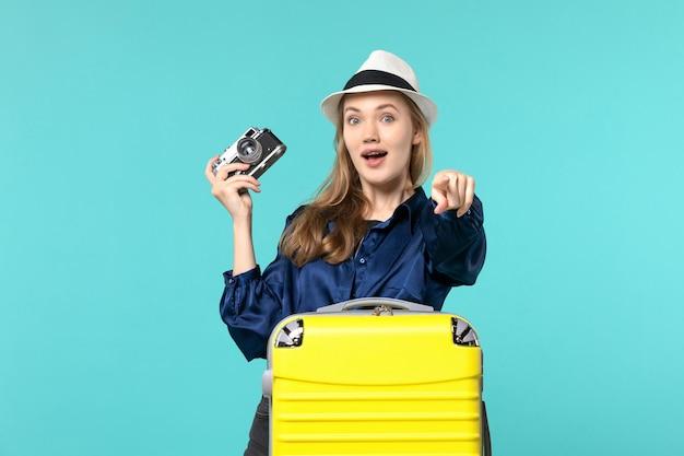 Widok z przodu młoda kobieta trzymając aparat na niebieskim tle kobieta podróż samolotem podróży morskiej