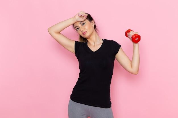 Widok z przodu młoda kobieta trzymając hantle na jasnoróżowej ścianie sportowiec ćwiczenia ćwiczenia