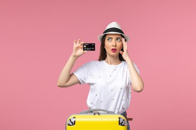 Widok z przodu młoda kobieta trzymająca czarną kartę bankową na różowej ścianie w kolorze podróży latem