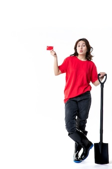 Widok z przodu młoda kobieta trzymająca czarną łopatę i kartę bankową na białym tle kobieta praca gleba kopanie praca ziemia noc kolor pieniądze